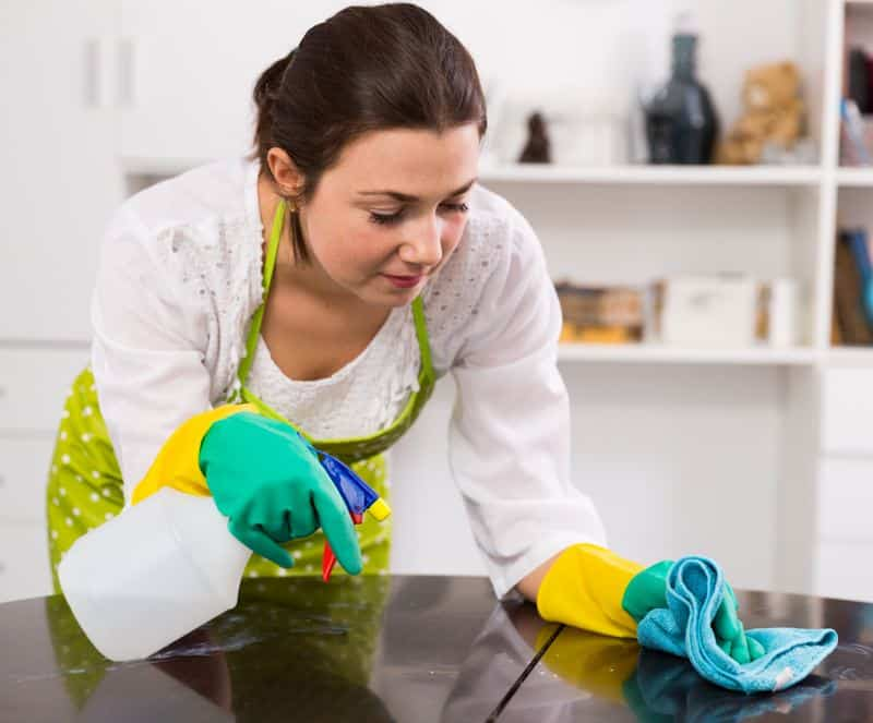 Mujer limpiando muebles de madera de la cocina